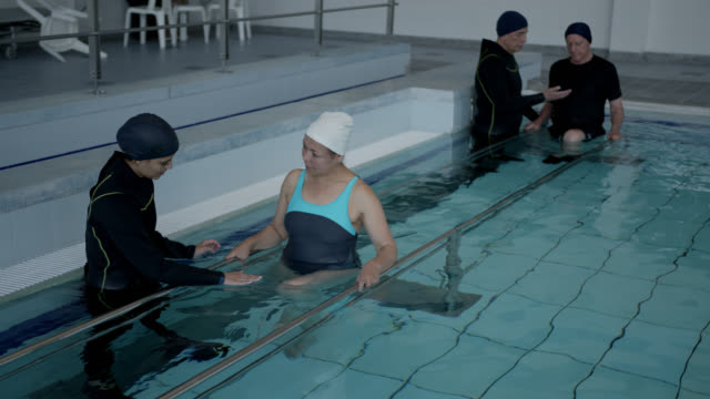 mixed age range of patients holding on to the parallel bars walking with the assistance of their therapists during hydrotherapy - mixed age range stock videos & royalty-free footage