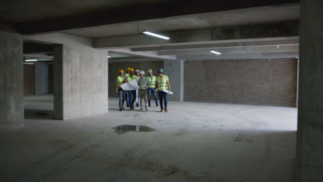 mixed age range of professionals inspecting a building under construction - mixed age range stock videos & royalty-free footage
