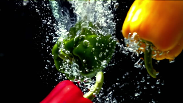 mixed colored paprika falling into water on black background super slow motion 1000 fps - bell pepper stock videos & royalty-free footage