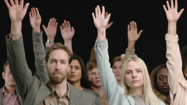 ms mixed crowd holding hands up in the air in slow motion. black background - medium group of people stock videos & royalty-free footage