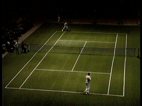 mixed doubles indoor game is being played / seated people applaud / two men speak / man serves and returns the ball / man speaks to the camera / play... - tennis racket stock videos & royalty-free footage