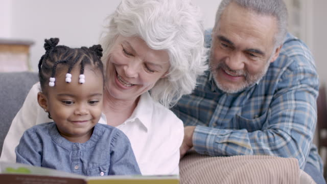 mixed ethnic couple grandparents spending time with their grandchild - grandchild stock videos & royalty-free footage