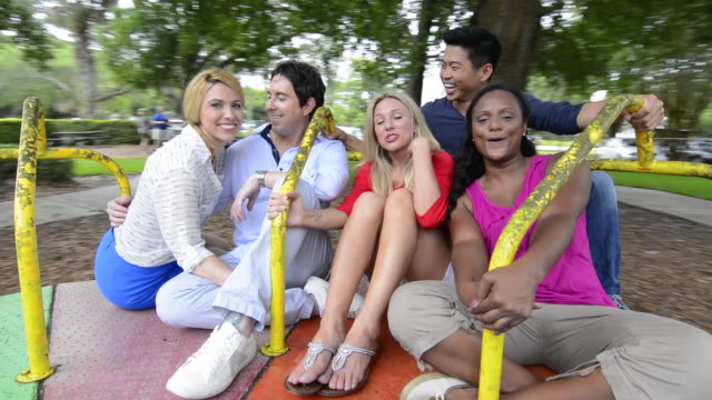mixed ethnic friends spinning on merry go round in playground laughing with black, vietnamese, hispanic, white people in their 20's and 30's MR-9, MR-5, MR-4, MR-6, MR-7 Model released