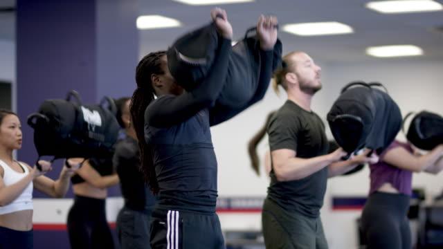 stockvideo's en b-roll-footage met een gemengde etnische groep fitness klasse een training samen met zandzakken - fatcamera