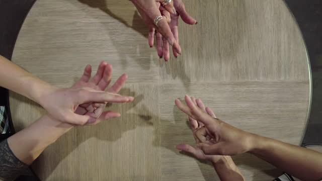 vidéos et rushes de mixed ethnic group playing paper scissors rock decision game série vidéo 4k - caillou