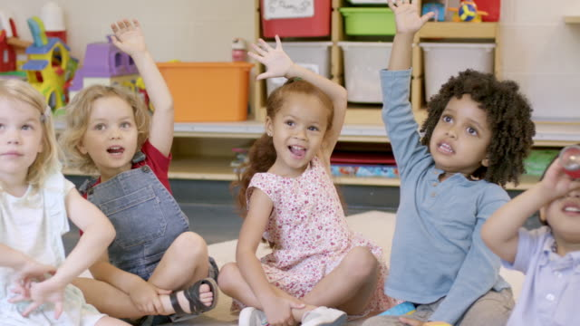 mixed ethnic preschool students in daycare - arms raised stock videos & royalty-free footage