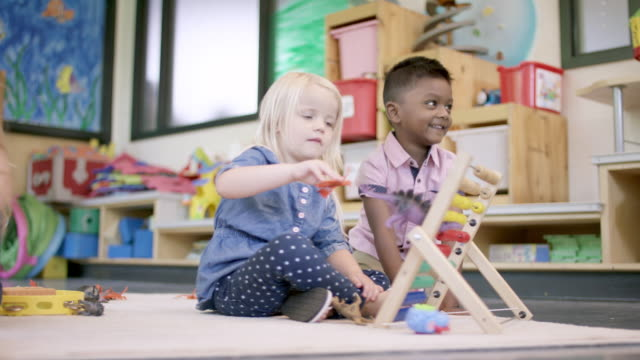 mixed ethnic preschool students playing in their classroom - child care stock videos & royalty-free footage