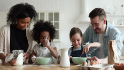 Mixed ethnicity children preparing pancakes helping parents cooking together