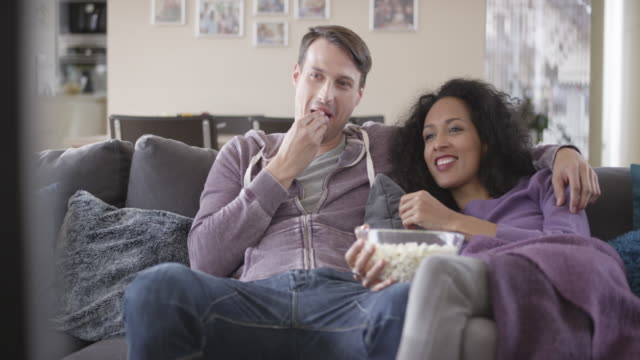 DS Mixed ethnicity couple watching TV and eating popcorn