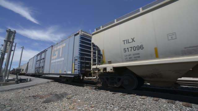 mixed goods freight train psses west thru downtown emporia - 貨物列車点の映像素材/bロール