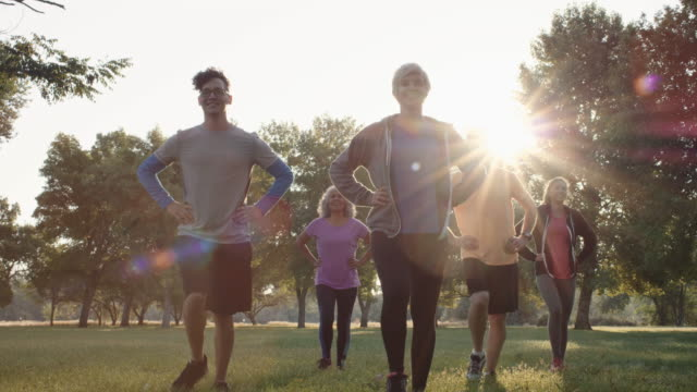 vídeos de stock e filmes b-roll de 4k slo mo: mixed group sunrise fitness - parque público