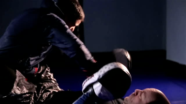 Mixed martial art fighters grapple and wrestle on the ground of a gym