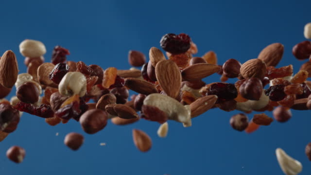 mixed nuts in the air on blue background - dried food stock videos & royalty-free footage
