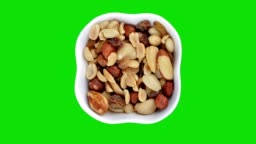 Mixed nuts in white bowl rotating on the green screen