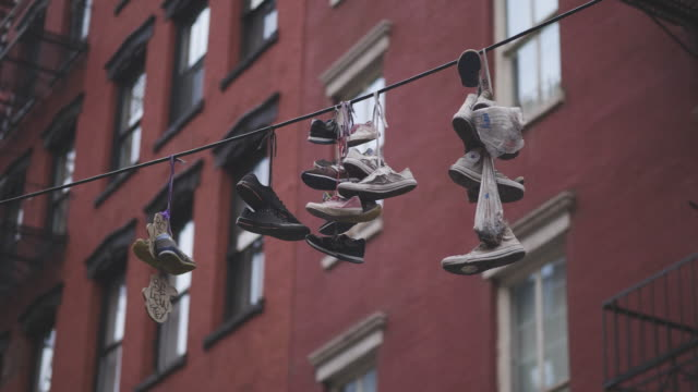mixed old shoes hanging on a wire - povertà video stock e b–roll