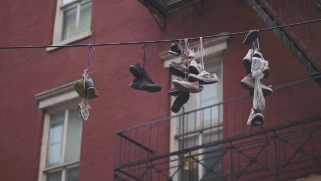 mixed old shoes hanging on a wire - differential focus stock videos & royalty-free footage