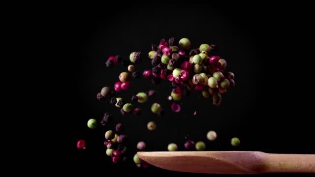 stockvideo's en b-roll-footage met mixed peppercorns op een lepel in super slow motion 1000 fps - peper specerij