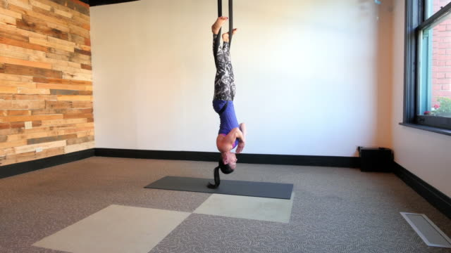 mixed race aerial yoga instructor working out on silks - upside down stock videos and b-roll footage