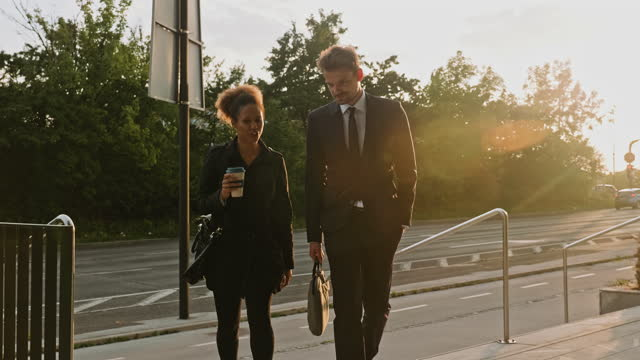 mixed race and caucasian colleagues walking and talking at sunset - side by side stock videos & royalty-free footage