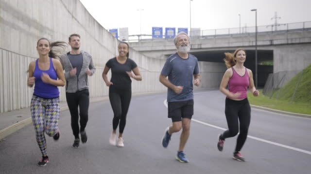 mixed race and caucasian runners on empty urban street - approaching stock videos & royalty-free footage