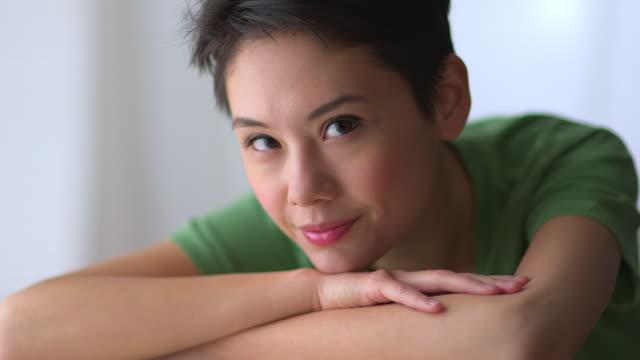 stockvideo's en b-roll-footage met mixed race asian woman smiling - natuurlijk haar