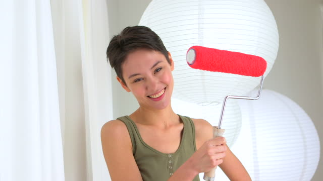 Mixed Race Asian woman with paint roller in home