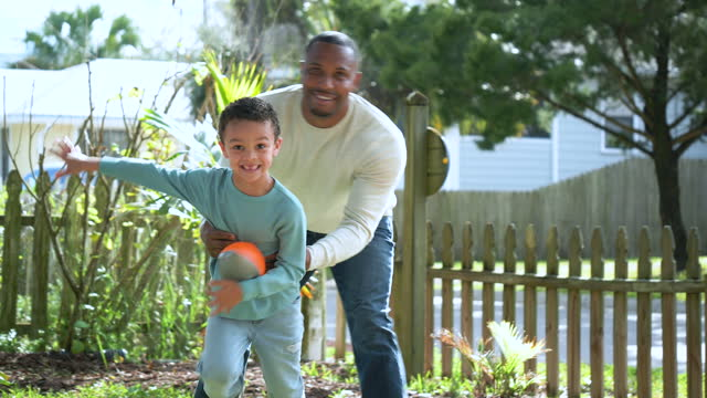 mixed race boy and father playing with football in yard - 4 5 years stock videos & royalty-free footage