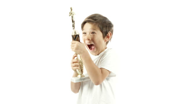 A mixed race boy celebrates with his trophy in slow motion.