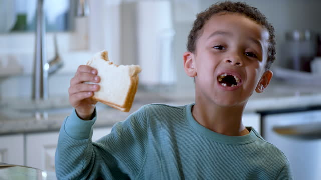 mixed race boy eating peanut butter sandwich - 4 5 years stock videos & royalty-free footage