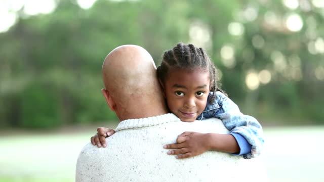 vídeos de stock, filmes e b-roll de menino da raça misturada nos braços do pai, olhando sobre o ombro - cabelo com trancinhas