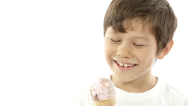 vídeos y material grabado en eventos de stock de un muchacho de raza mixta lame su helado felizmente. - lamer