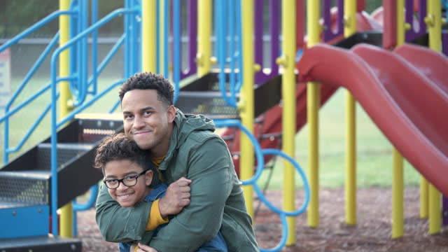 mixed race boy on playground with father, hugging - 10 11 years stock videos & royalty-free footage