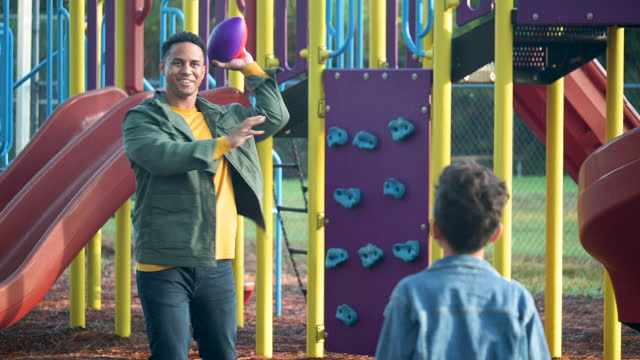 mixed race boy on playground with father playing catch - team sport stock videos & royalty-free footage