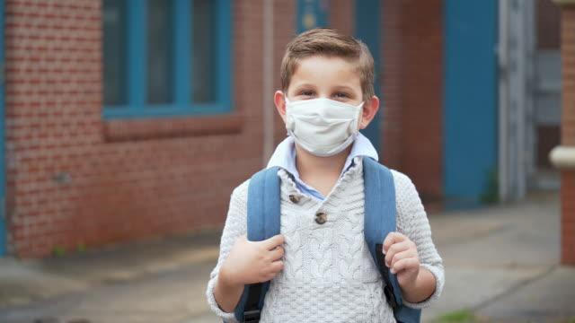 mixed race boy outside elementary school wearing mask - elementary school building stock videos & royalty-free footage