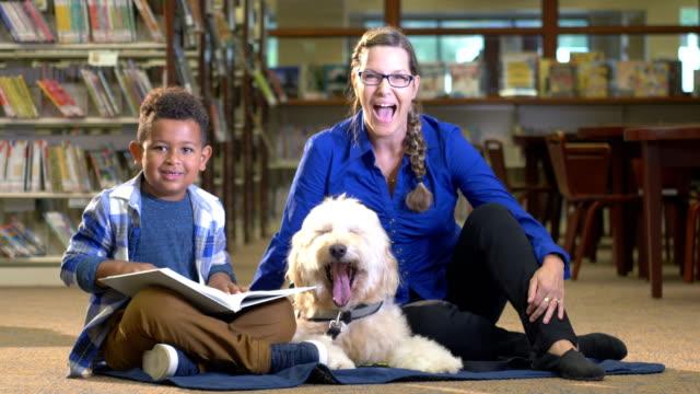 Mixed race Boy lezing in bibliotheek met therapie hond