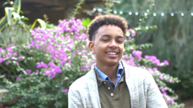 blandad ras pojke som står i parken leende på kameran - 12 13 år bildbanksvideor och videomaterial från bakom kulisserna