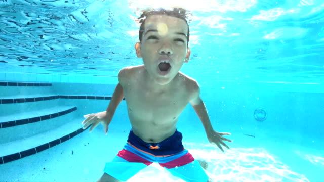 mixed race boy swimming in pool underwater - swimwear stock videos & royalty-free footage
