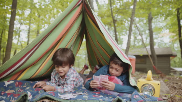 mixed race boys playing card game in blanket tent - camping stock videos and b-roll footage