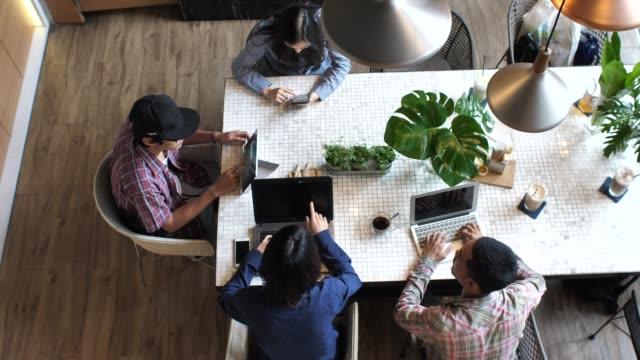 mischlinge-business-team in loftbüro und arbeiten am tisch sitzen - loft stock-videos und b-roll-filmmaterial