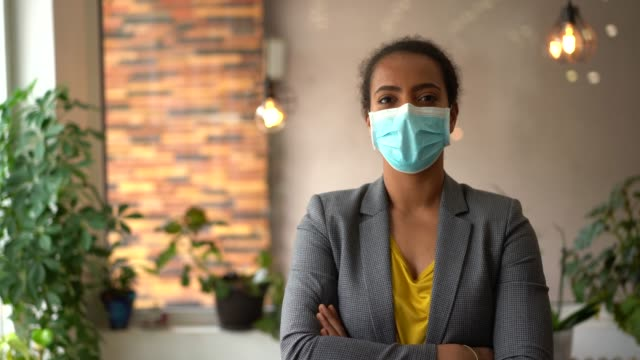 mixed race businesswoman looking at camera - health and safety stock videos & royalty-free footage