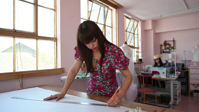 mixed race costume designer creating pattern in pink atelier - workbench stock videos & royalty-free footage