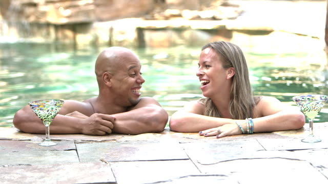 Mixed race couple at resort swimming pool