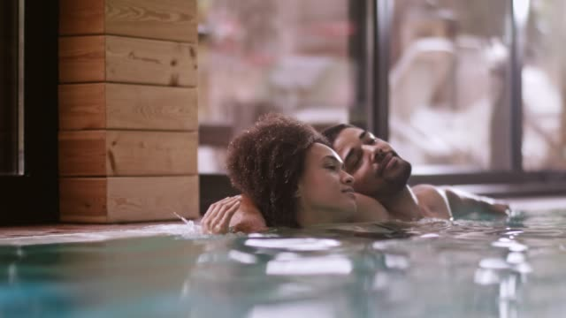 mixed race couple enjoying at spa pool - mid adult couple stock videos & royalty-free footage
