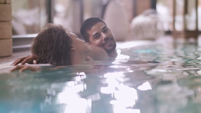 Mixed race couple enjoying at spa pool