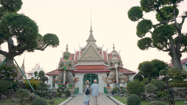 mixed race couple happy tourists to travel on they holidays and holding travel map and pointing in wat arun temple in bangkok, thailand - pagoda stock videos & royalty-free footage