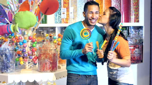 mixed race couple in a candy store - young women stock videos & royalty-free footage