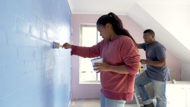 vídeos de stock, filmes e b-roll de mixed race couple painting a wall in their bedroom - quarto de dormir