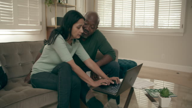ms mixed race couple using their pc laptop at home - black hair stock videos & royalty-free footage