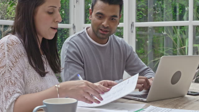 mixed race couple working on the home finances at home - online banking video stock e b–roll