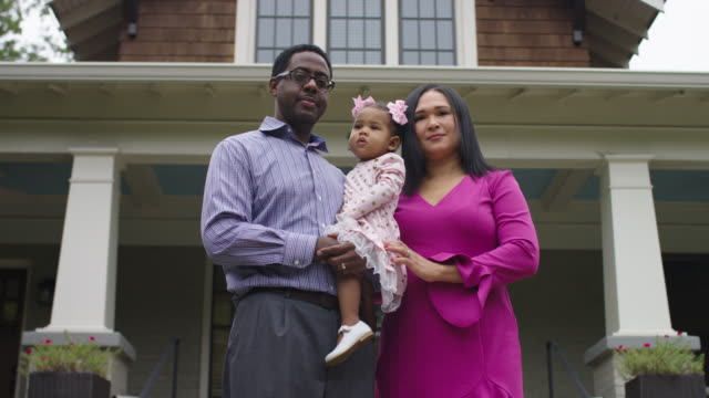mixed race family in front of house - front view stock videos & royalty-free footage